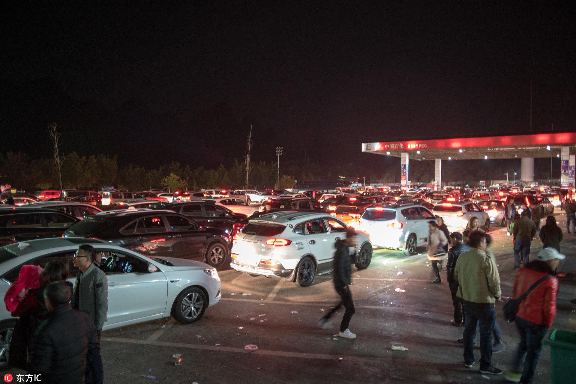 2018年2月2日凌晨5点,G65高速广西桂林境内,等待进服务区的车辆排队数十公里,有返乡的旅客下车散步。