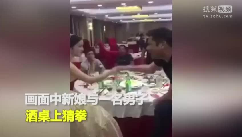 女子身披婚纱酒桌上划拳