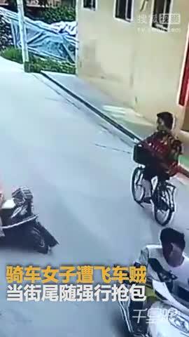 骑车女遭飞车贼当街抢包